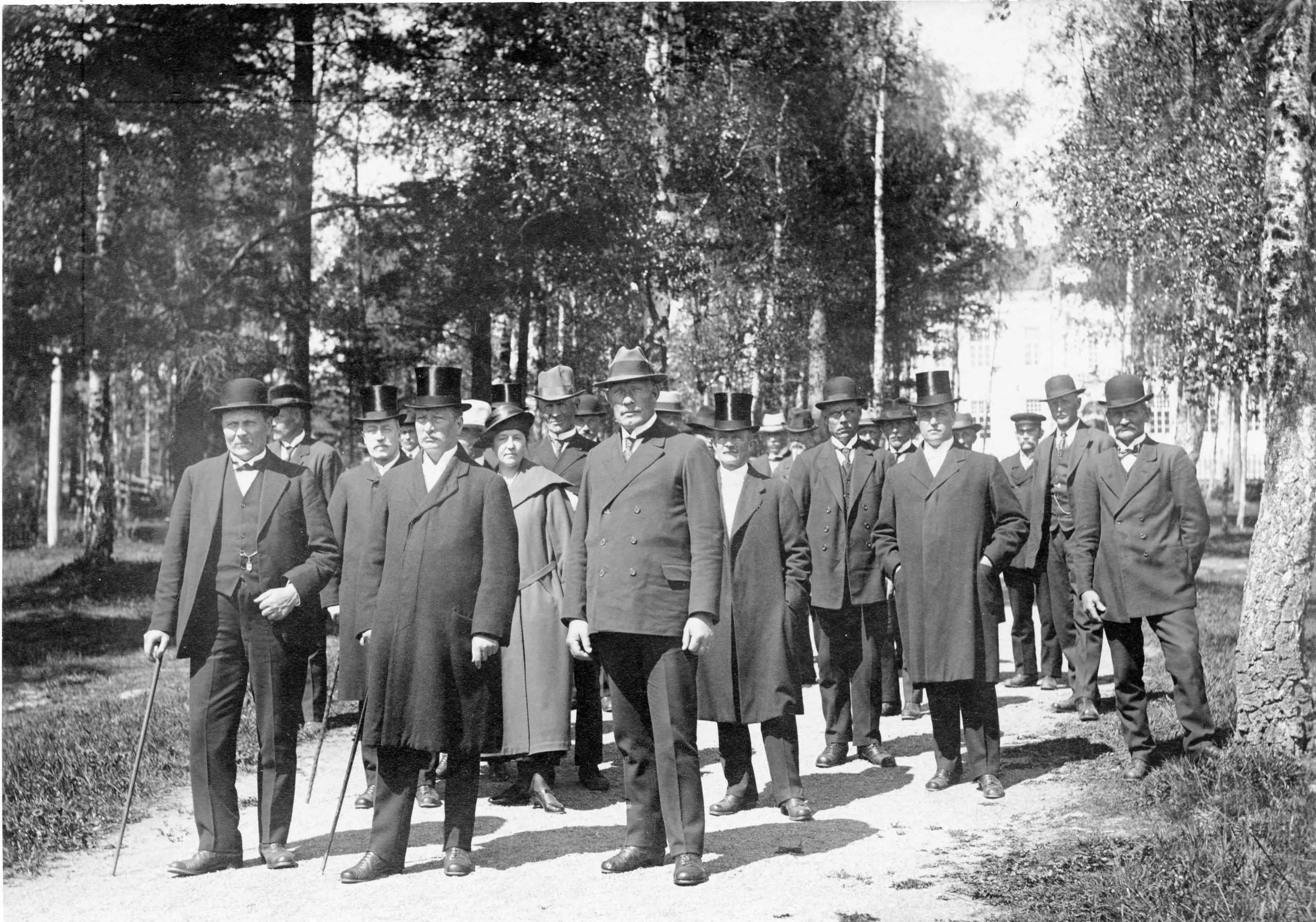 Medlemmar av Ålands landsting på väg till kyrkan i Mariehamn. På bilden ses bl.a. Johannes Eriksson, August Karlsson, Julius Sundblom och Fanny Sundström. Ålands Museum